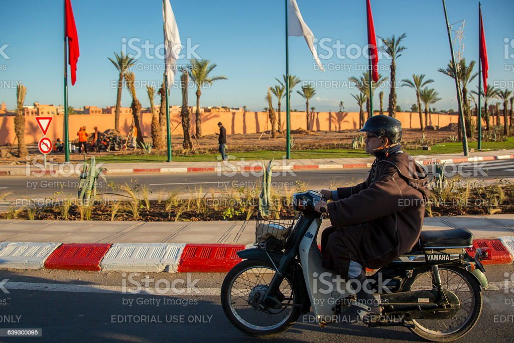 Motorcycle driver on the road in Marrakesh stock photo