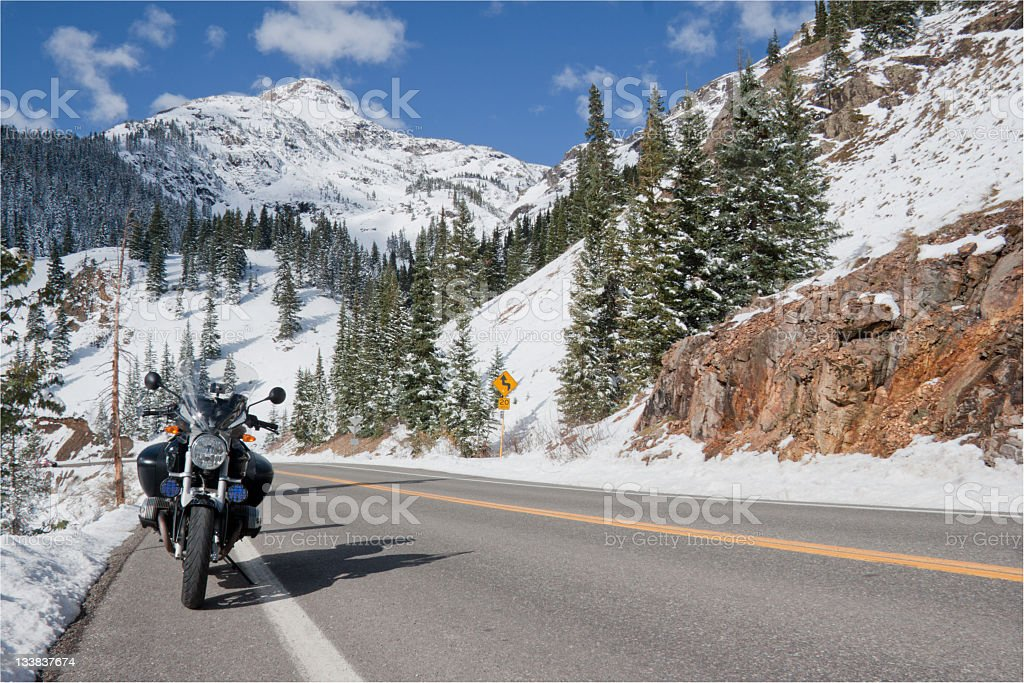 Motorcycle parked along a snowy highway in the Rockies. stock photo