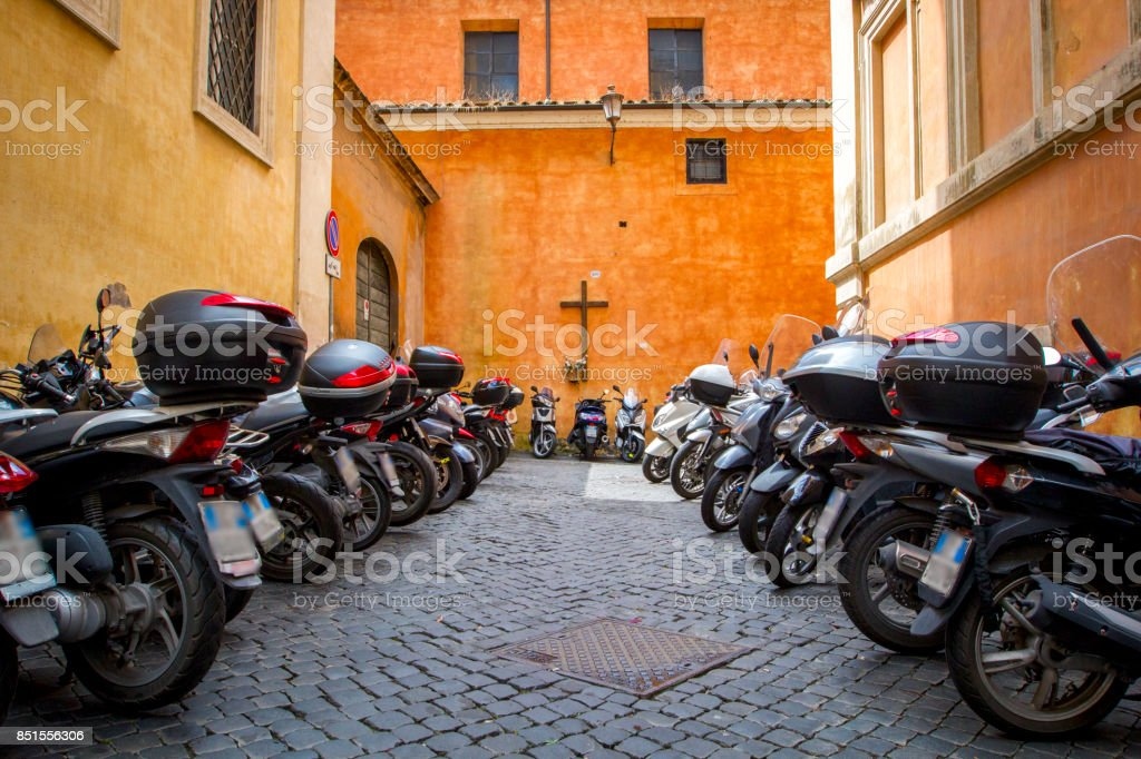 Motorcycle parking next to the terrace of a church. Rome, Italy. The motorcycle is one of the most used transport in the city of Rome. stock photo