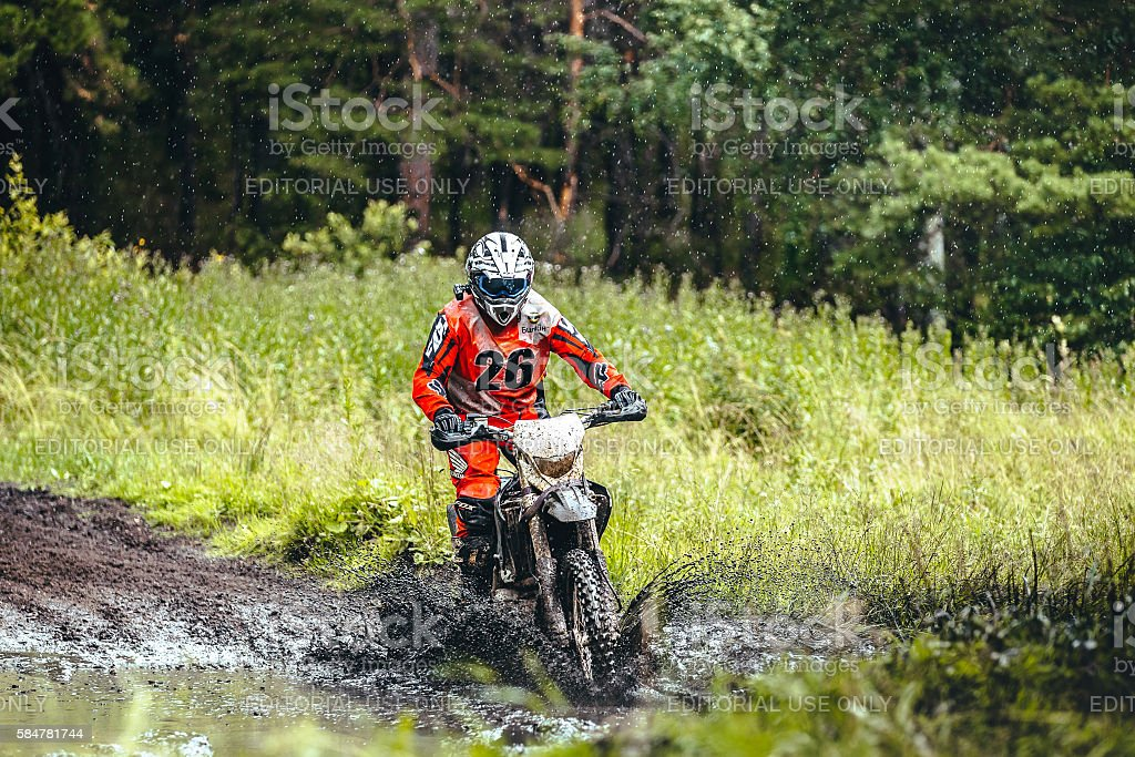 motorcycle racer rides in a puddle of mud in woods royalty-free 스톡 사진