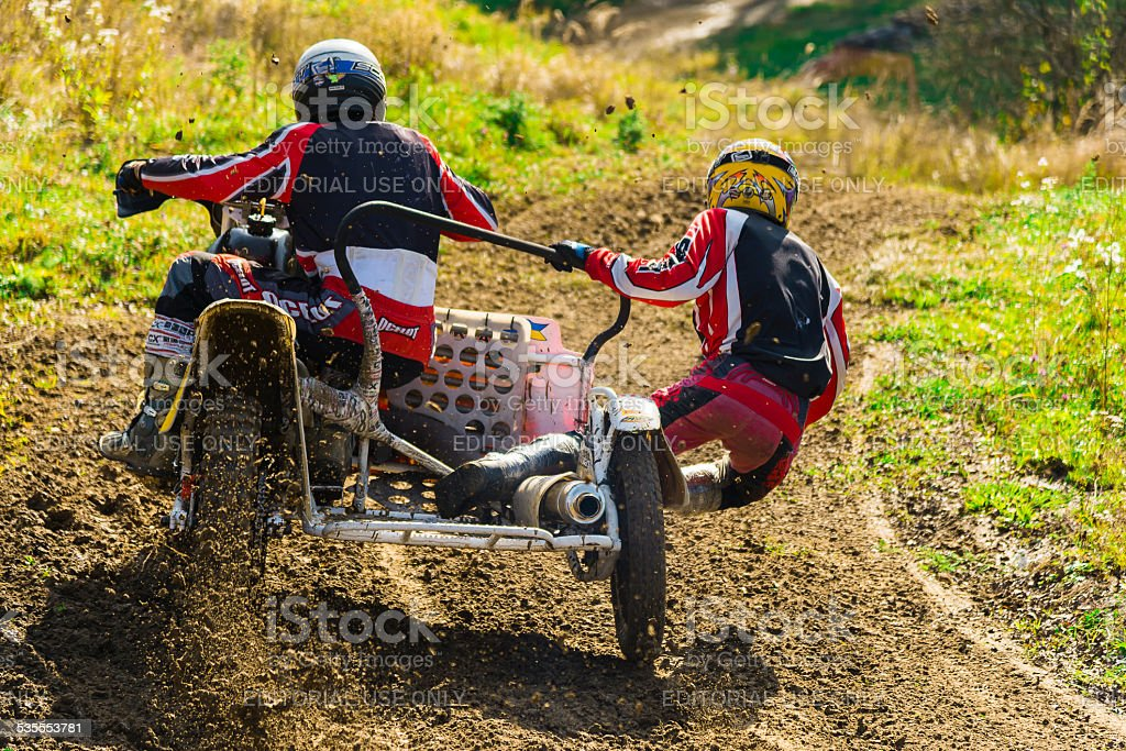 Motorcycle racers on motorcycles with sidecars overcome steep turn stock photo