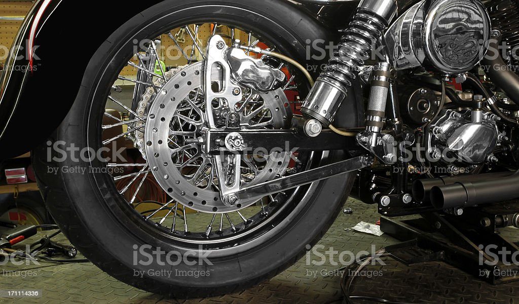 Motorcycle under construction in home garage.  Wheel dominant. stock photo