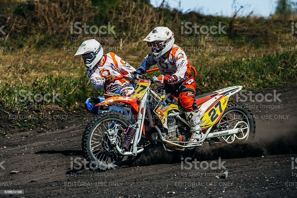 motorcycle with sidecars riding along a dusty track stock photo