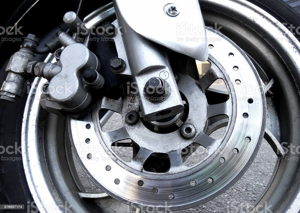 Motorcycle worn disc and caliper of hydraulic brake system stock photo