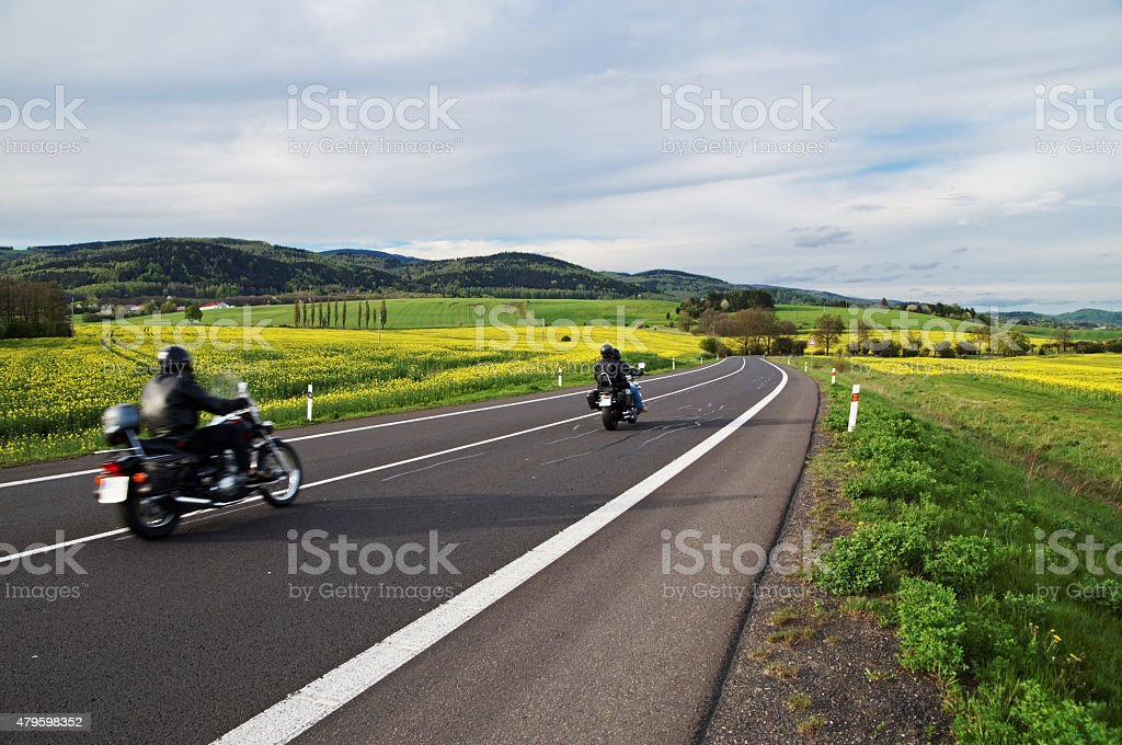 Motorcycles traveling along an empty road between blooming rape fields stock photo