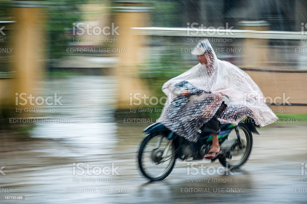 Motorcycling Through A Rain Storm In Vietnam stock photo