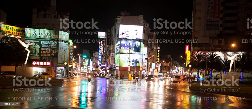 Motorcyclist a crosses road junction at night, Hualien, Taiwan stock photo