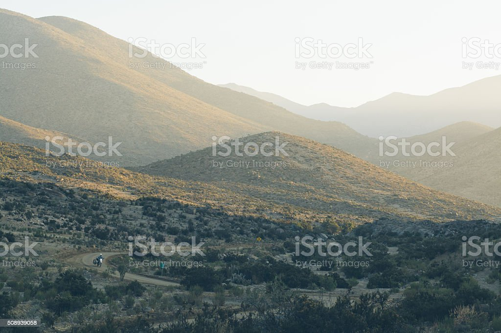 Motorcyclist in the mountains at sunset stock photo