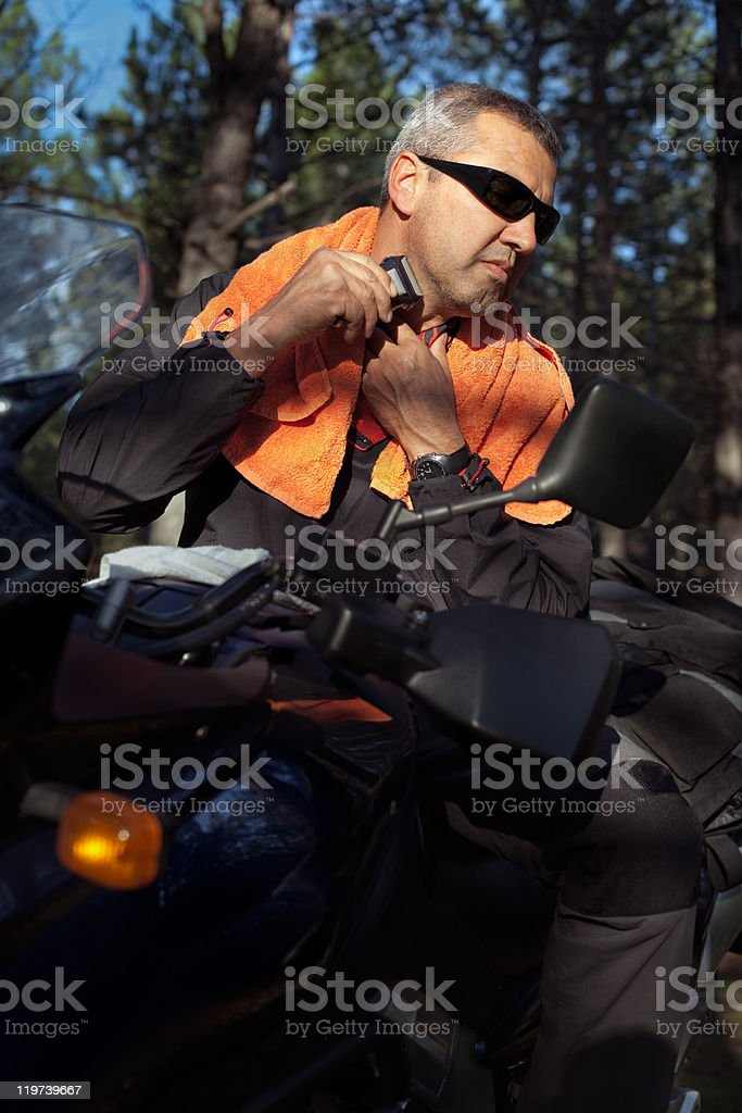 Motorcyclist Man Shaving With Electric Razor On Motorcycle royalty-free stock photo