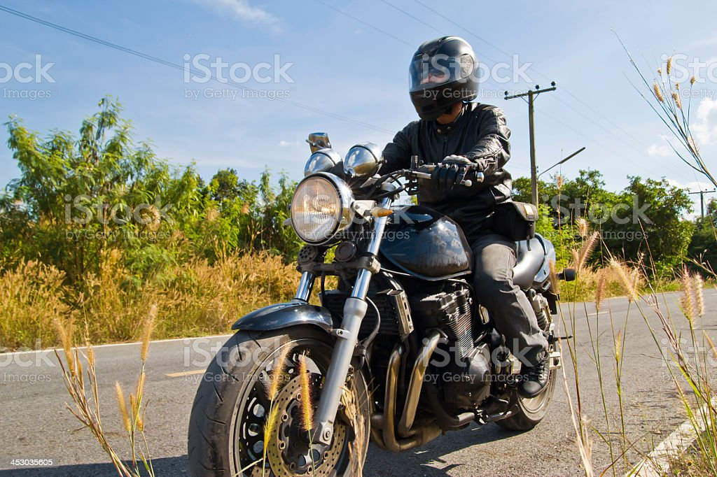 Motorcyclist on asphalt country road stock photo