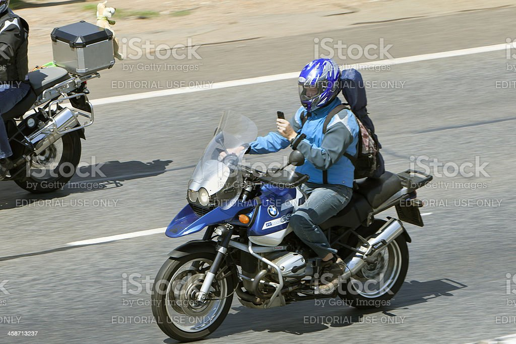 Motorcyclist on mobile phone and riding stock photo