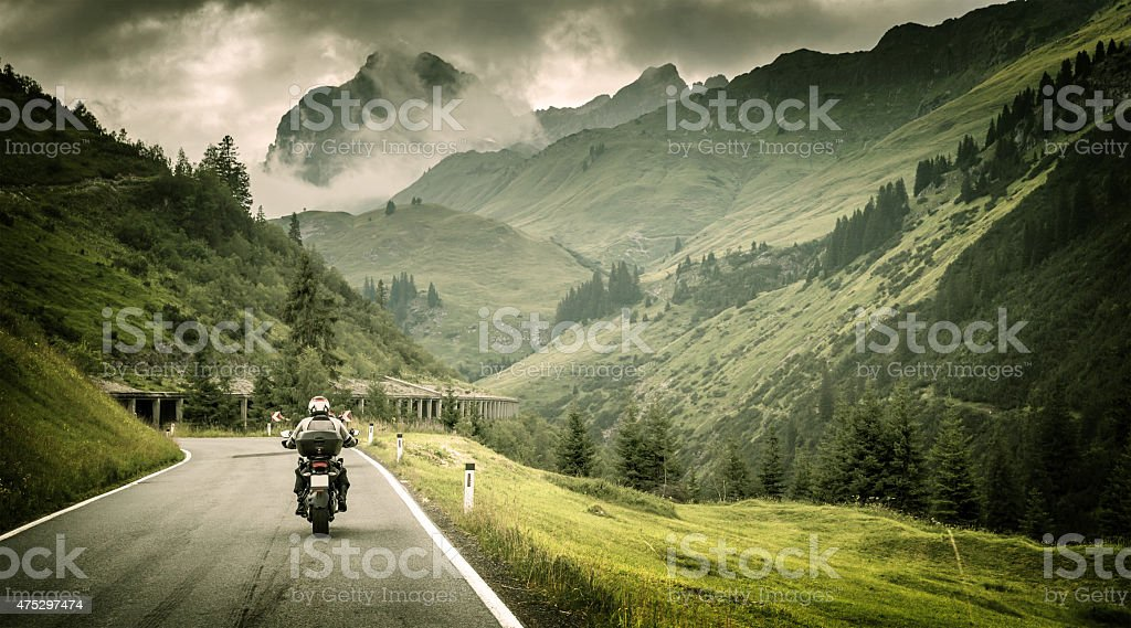 Motorcyclist on mountainous highway stock photo
