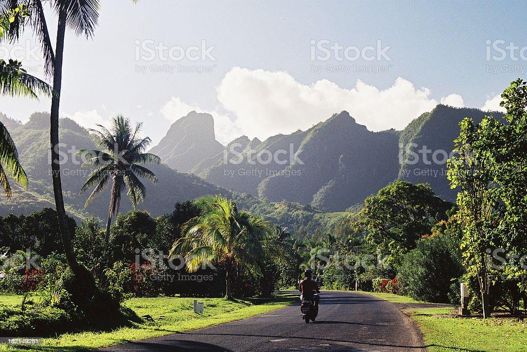 Motorcyclist on Polynesian road stock photo