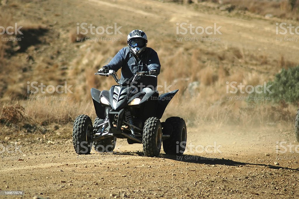 A motorcyclist riding a quadbike in an arid area stock photo