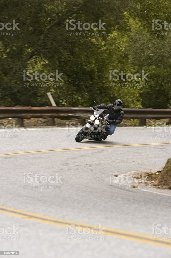Motorcyclist taking corner stock photo