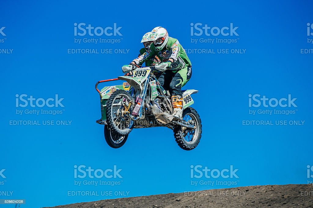 motorcyclist with a sidecar jump from a mountain stock photo