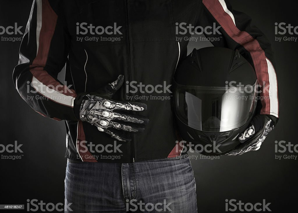 Motorcyclist with helmet in his hands. Dark background stock photo