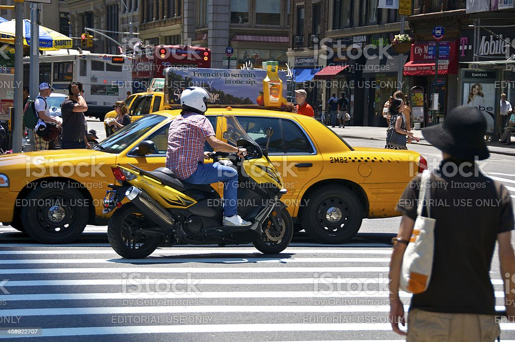 Motorcyclist, Yellow Taxi & pedestrians at E.23rd St, Manhattan, NYC royalty-free stock photo