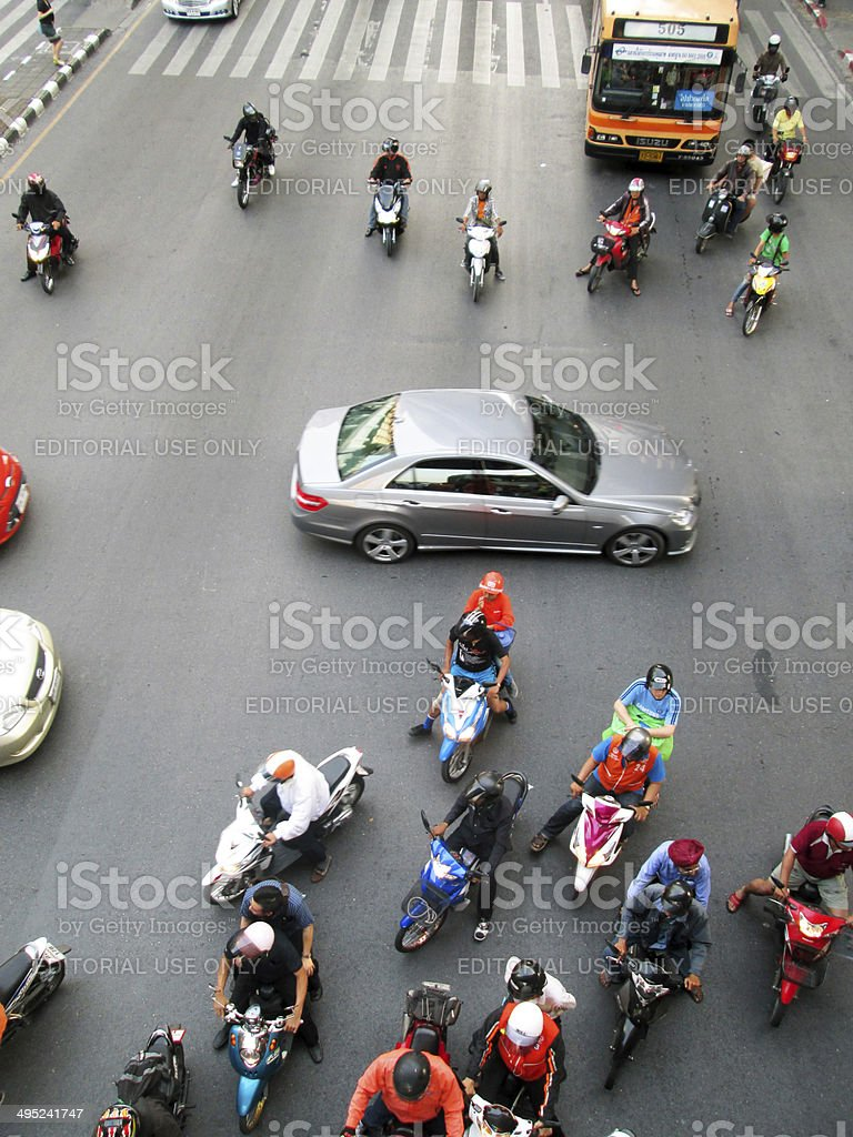 Motorcyclists and cars wait at a junction during rush hour royalty-free stock photo