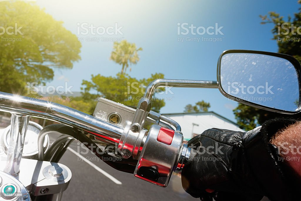 Motorcyclist's hand on handlebar as bike drives along tree-lined road stock photo