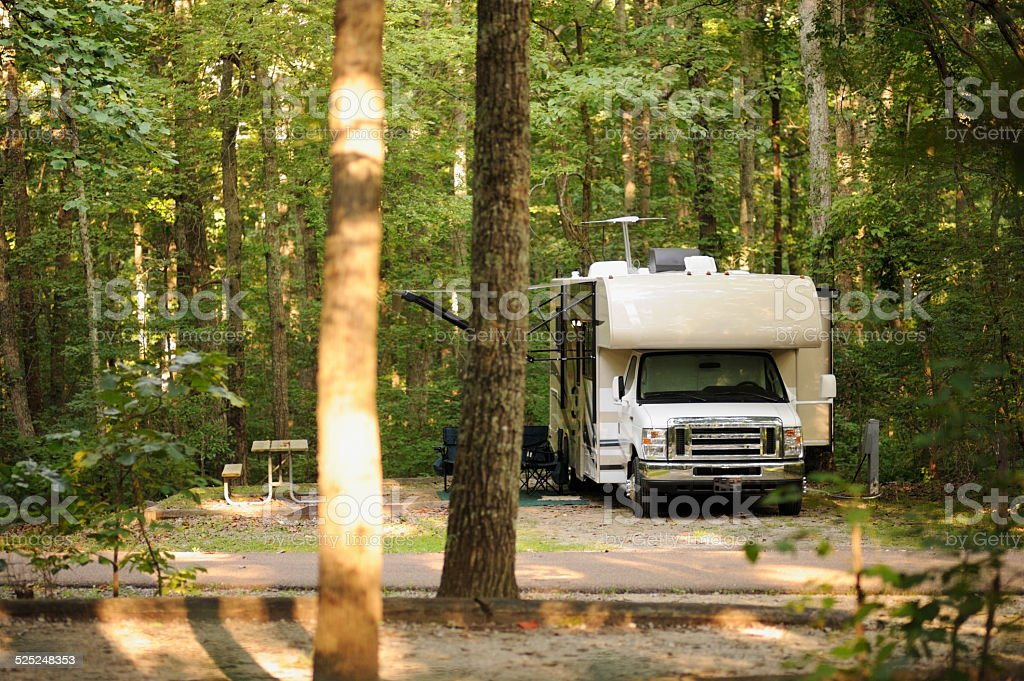 Motorhome in wooded campsite stock photo