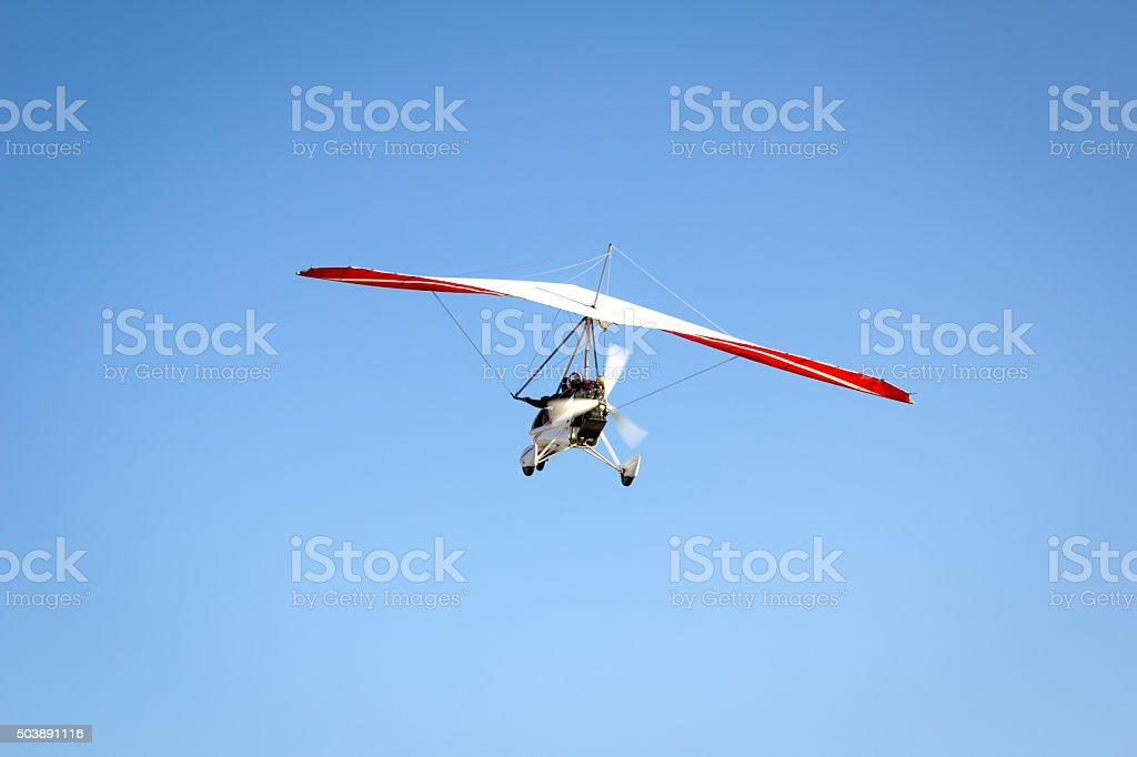 Motorized hang glider soaring in the blue sky stock photo