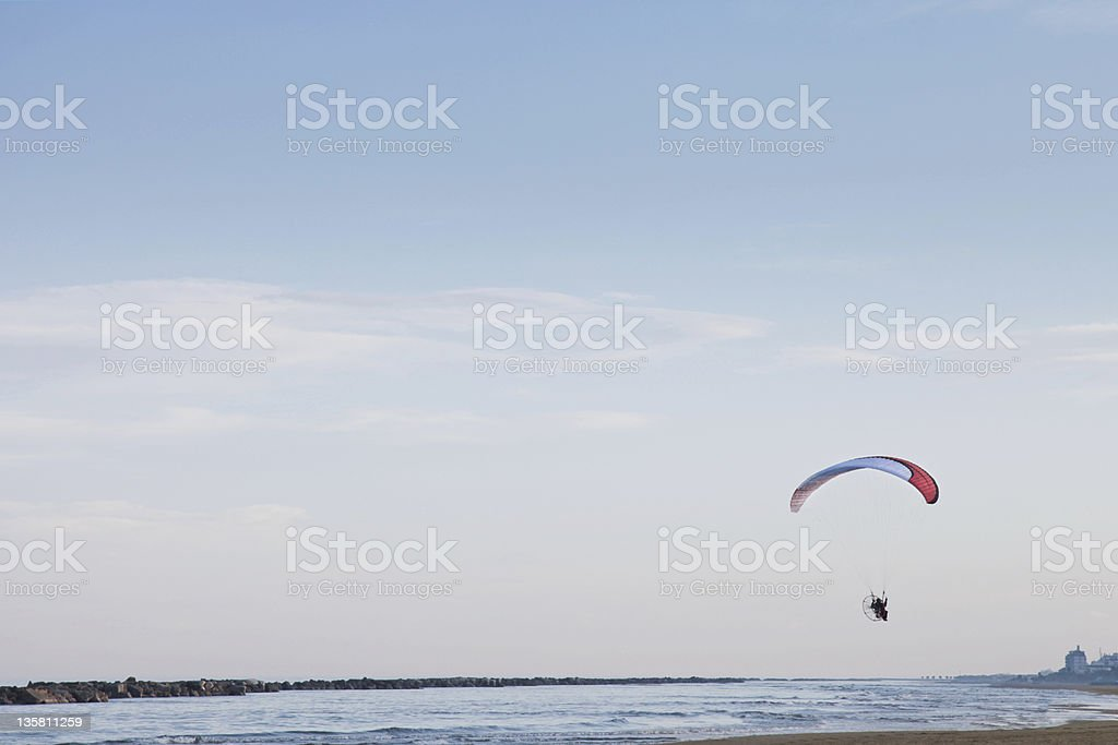 Motorized paraglider flies over the sea stock photo