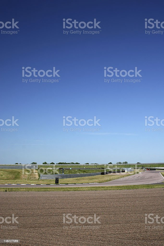 A motorsport track under a vivid blue sky. The track comes in from...