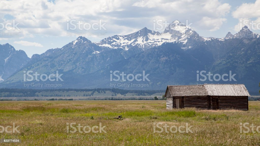 Moulton barn located in Mormon Row, Gros Ventre River Valley in Grand Teton National Park and active cloudy sky in background stock photo