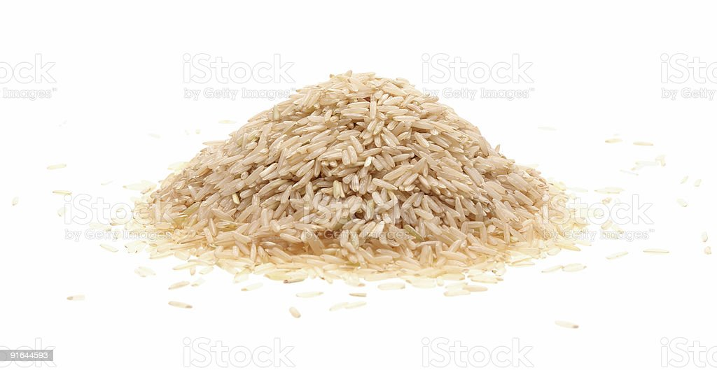 A mound of brown rice grains isolated on white stock photo