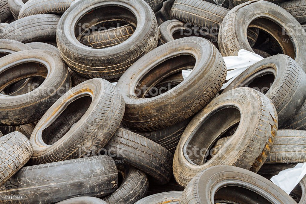 Mound of used car tires in a junkyard stock photo