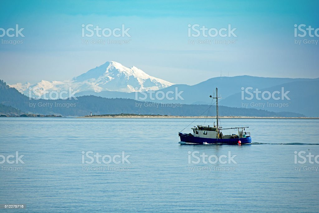 Mount Baker, in Washington, and  fishing boat on calm water stock photo