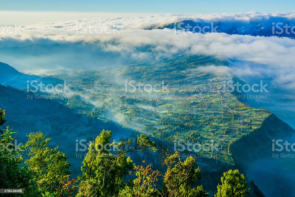 Mount Bromo volcano during sunrise, with foggy moment stock photo