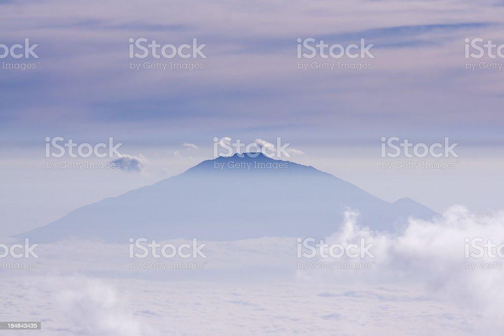 Mount Meru towering over morning haze stock photo