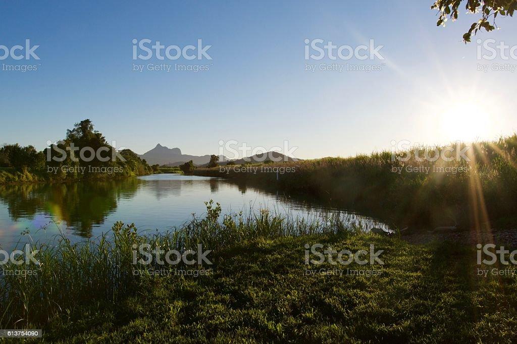 Mount Warning, river, sugar cane and sun stock photo
