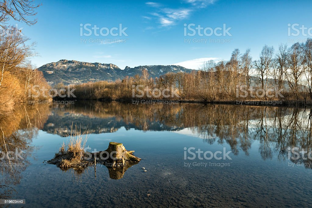 mountain and trees reflection in lake at springtime stock photo