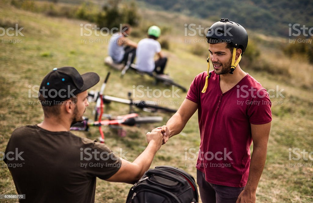 Mountain bike cyclist fist bumping with is friend in nature. stock photo
