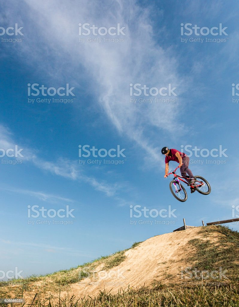 Mountain bike cyclist performing straight air jump over dirt hill. stock photo