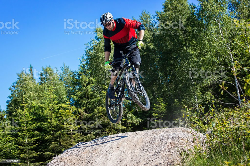 Mountain bike rider jumping kicker stock photo