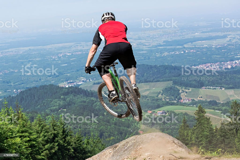 Mountain bike rider jumping precipice stock photo