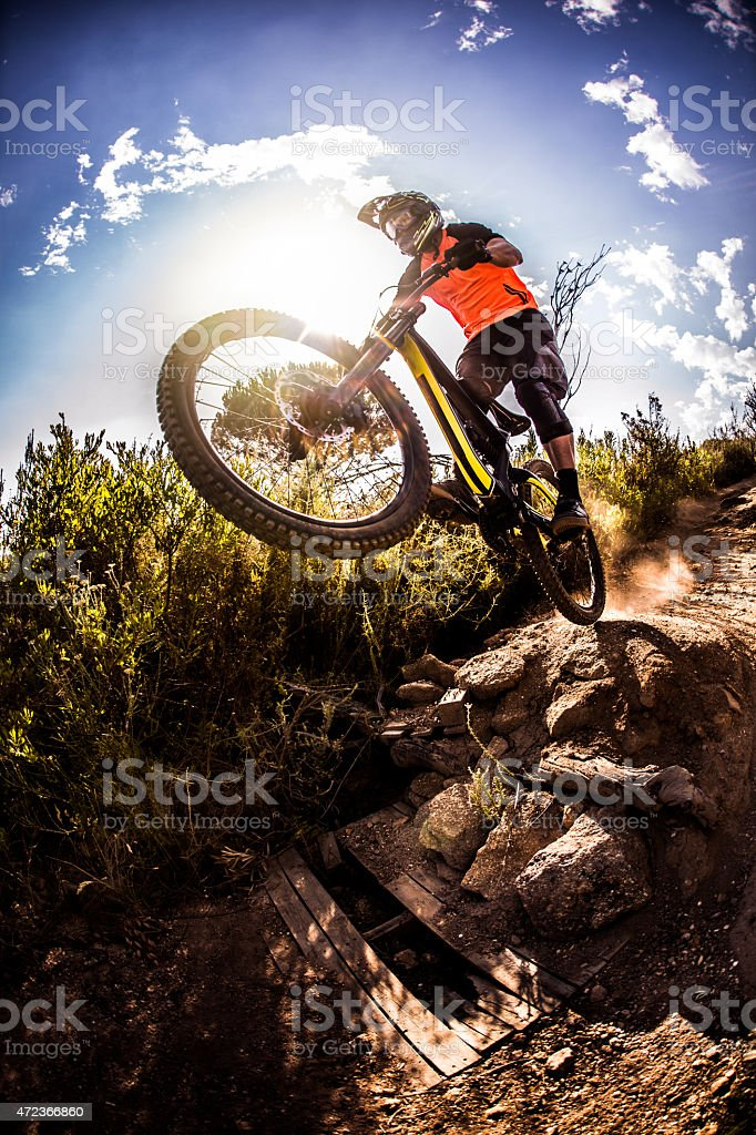 Mountain biker about to dirt jump over rough terrain stock photo