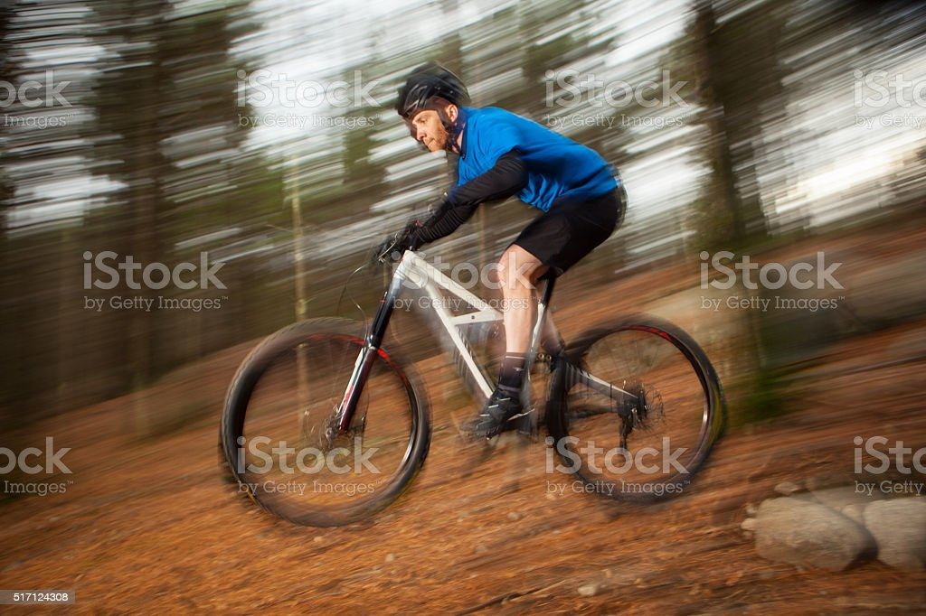 Mountain biker catching air during a downhill run. stock photo