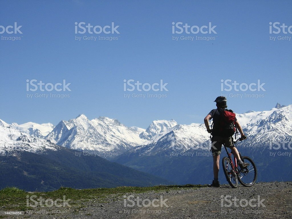 Mountain biker enjoying a view of the alps royalty-free stock photo