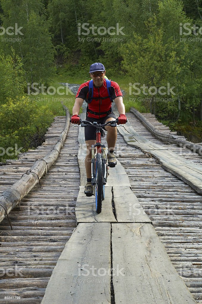Mountain biker goes on old wooden bridge royalty-free stock photo