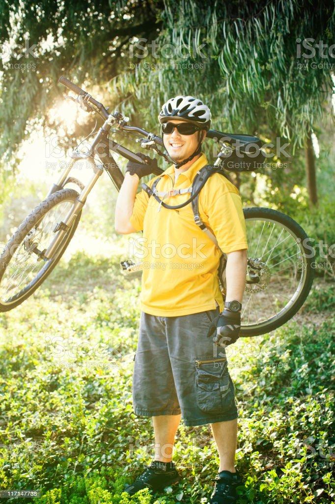 Mountain biker holding bike on sholder stock photo