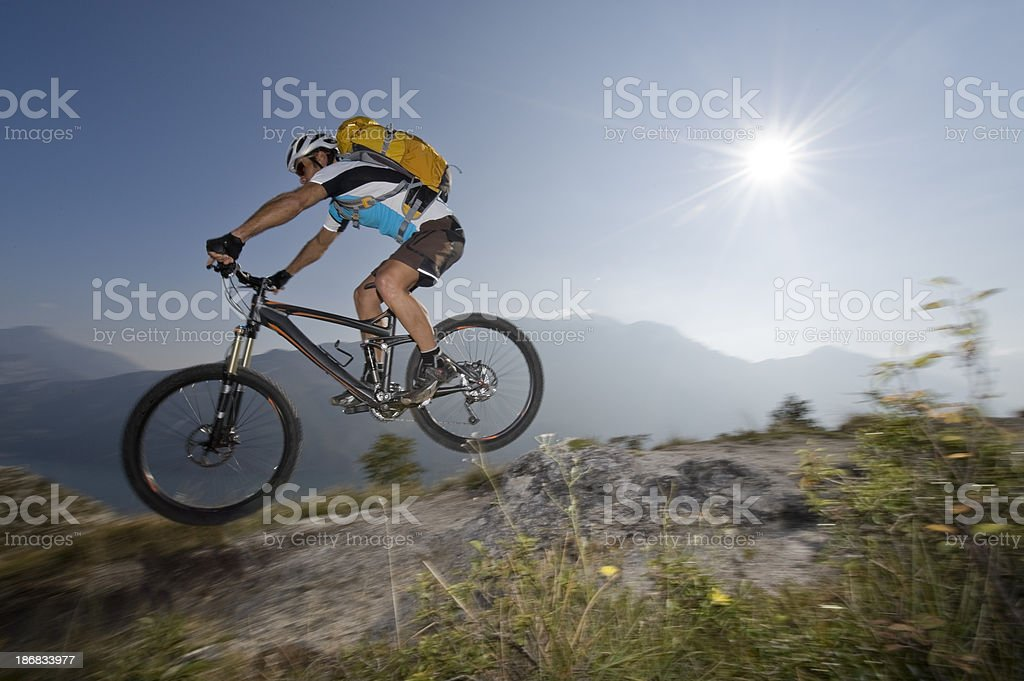 Mountain biker in the back light jumping stock photo