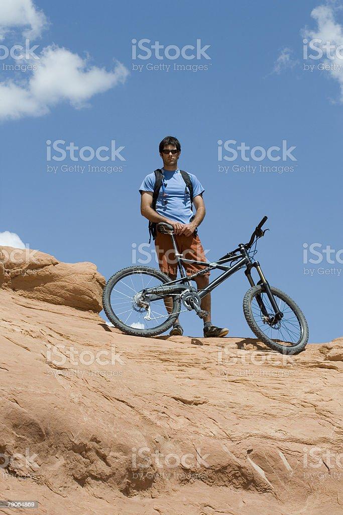 Mountain biker on rock stock photo