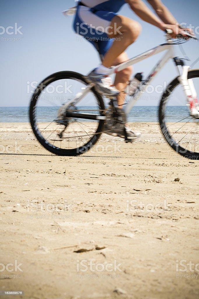 Mountain biker on the beach stock photo