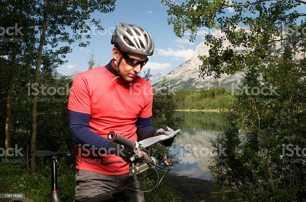 Mountain Biker Reading a Map royalty-free stock photo