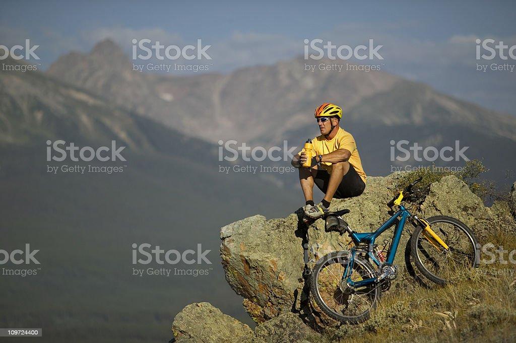 Mountain Biker Resting on Rock royalty-free stock photo